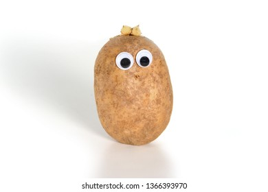 Googly eyes. Funny cute brown mister Fresh Potato on white background.