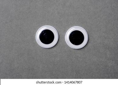 Googly eyes on grey background looking straight forward..