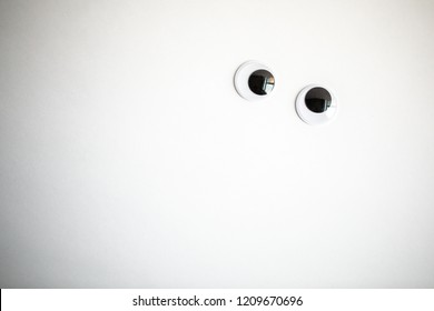 Googly eyes on a white background shot close up
