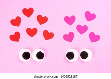 Googly eyes of strange pair of lovers on rose background with some small hearts. Close-up toy eyes