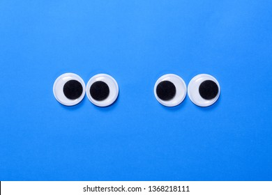 Googly eyes: Two pair strabismus and squint mad googly eyes next to each other on blue background.