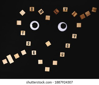 Googly eyes with wooden letters forming a heart spelling a romantic message