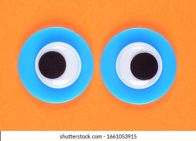 Googly toy eyes. Neon green mad strabismus eyes look straight at you, on a background of orange paper. Macro close up.