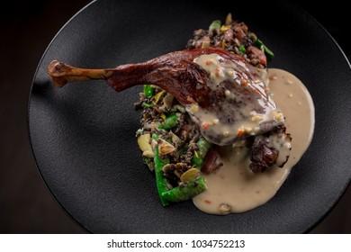 goose leg confit with sugar snap peas and black lentils