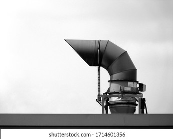 goose neck shaped mechanical vent pipe on roof top with ties and braces and metal parapet flashing. black and white presentation. building mechanics and construction concept.