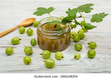 Gooseberry jam and fresh berries, on a light wooden background