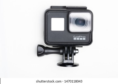GoPro Hero 7 black action camera mounted on simple tripod accessory against a white background with a reflection on the lens