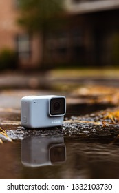 GoPro Hero 7 White action camera on the street near a puddle with reflection during autumn in Baton Rouge Louisiana USA - December 31 2018