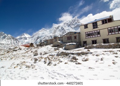 Gorak Shep, Everest Region, Nepal - March 19, 2010: The hotels in Gorak Shep village on snowy ground with high snow mountains behind in bright blue sky and white cloud.