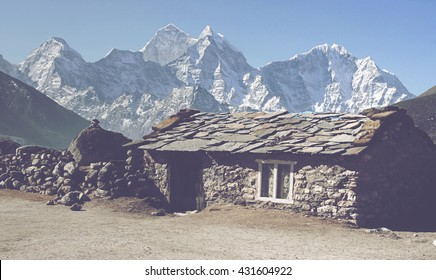 GORAK SHEP, NEPAL - CIRCA MARCH 2010: Exterior view of single cute stone block cabin with view of the Himalayan mountain peaks under bright blue sky. Gorak Shep, Nepal circa March 2010.