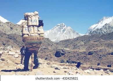 GORAK SHEP, NEPAL - CIRCA MARCH 2010: Sherpa carrying a large load on his back as he carries provisions for a mountaineer during a trekking expedition in Nepal.Circa March, 2010 in Gorak Shep, Nepal