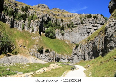 Gordale Scar, an iconic limestone ravine 1 mile northeast of Malham, North Yorkshire, England. It contains two waterfalls and has overhanging limestone cliffs over 100 metres high.