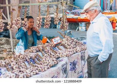 Gordes, Provence-Alpes-Cote d'Azur, France, September 25, 2018: An old gray-haired man trades with a seller of garlic and spices - a traditional farmers market in Provence