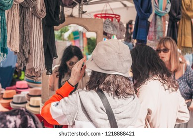 Gordes, Provence-Alpes-Cote d'Azur, France, September 25, 2018: Chinese tourist trying on hat - traditional farmers market in Provence