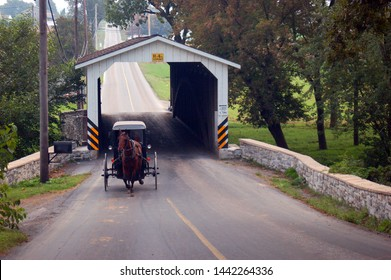 Gordonville, PA, USA September 18, 2006 An Amish horse and buggy emerge from a covered bridge near Gordonville, Pennsylvania