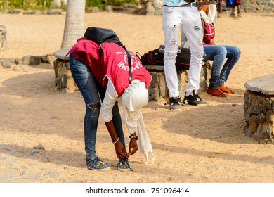 GOREE, SENEGAL - APR 28, 2017: Unidentified Senegalese woman bends down to tie shoelaces on the Goree Island, the former slave isle
