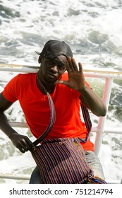 GOREE, SENEGAL - APR 28, 2017: Unidentified Senegalese man in red shirt and cap sails on boat in the Atlantic ocean near the Goree Island