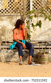 GOREE, SENEGAL - APR 28, 2017: Unidentified Senegalese girl with braids sits on the Goree Island, the former slave isle