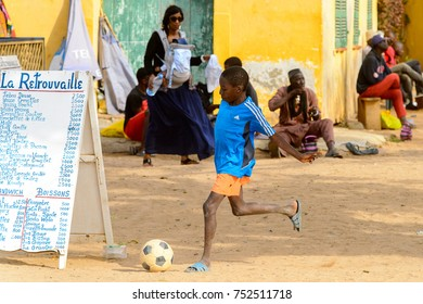 GOREE, SENEGAL - APR 28, 2017: Unidentified Senegalese little boy plays football on the Goree Island, the former slave isle