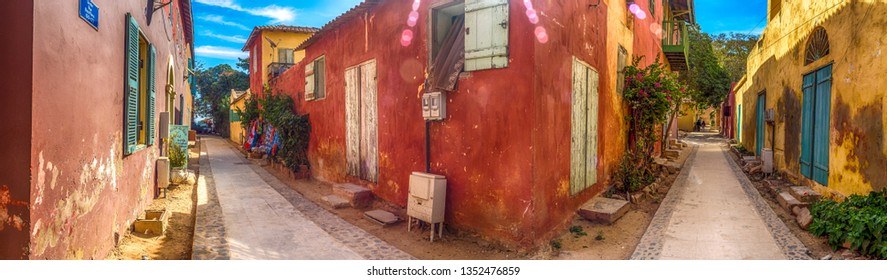 Goree, Senegal- February 2, 2019: Panoramic view of the street with a cobblestone road between colorful houses on the island of Goree. Gorée. Dakar, Senegal. Africa.
