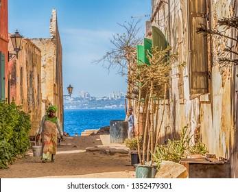 Goree, Senegal- February 2, 2019: Daily life, sandy road on the Goree island  and view of the city of Dakar Gorée. Dakar, Senegal. Africa.