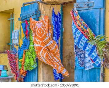 Goree, Senegal - February 2, 2019: Typical souvenirs, colorful dresses and pants from the island of Goree blowing in the wind.Gorée. Dakar, Senegal. Africa.