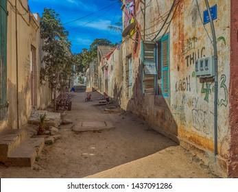 Goree, Senegal- February 2, 2019: Sandy street between the destroyed houses on the Goree island. Gorée. Dakar, Senegal. Africa.