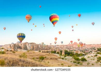 Goreme, Cappadocia / Turkey - 07-15-2018 : Colorful hot air balloons flying over at fairy chimneys in Nevsehir, Goreme, Cappadocia Turkey. Hot air balloon flight at spectacular Cappadocia Turkey
