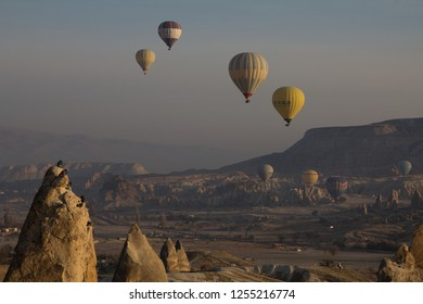 Goreme, Cappadocia, TURKEY - 15 November 2018: Hot air balloons flying over rock landscape at Cappadocia Turkey. Views from the observation deck in Goreme. Tourists on viewpoint and on air balloon
