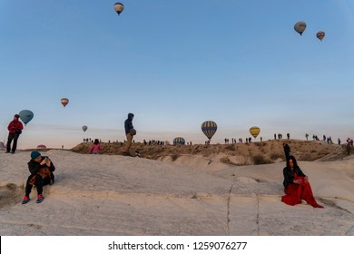 Goreme, Cappadocia, Turkey - October 31, 2018: Young man taking photos of a beautiful girl in Goreme Cappadocia