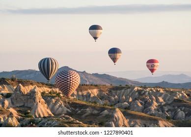 Goreme, Kapadokya / Turkey - 21 June 2017: Colorful hot air balloons in the air above beautiful rocks
