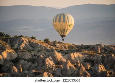 Goreme, Kapadokya / Turkey - 21 June 2017: Yellow hot air balloon flying over scenic rocks in Cappadocia