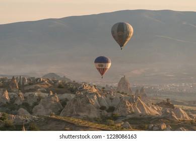 Goreme, Kapadokya / Turkey - 21 June 2017: Big and small hot air balloons flying together over beautiful rocks