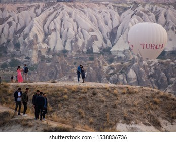 Goreme / Turkey - 09.27.2019: Balloon show over Goreme at dawn. Hundreds of balloons in the air over the city, mountains, pink and white valleys.