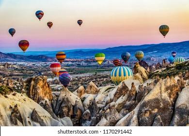 Goreme, Turkey / April 6, 2016 - Numerous hot air balloons all lift into the air just after dawn