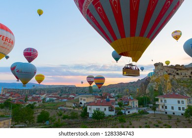 Goreme, Turkey / April 6, 2018 - Numerous hot air balloons all lift into the air just after dawn