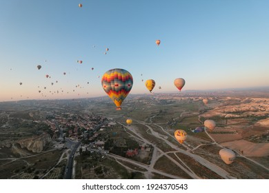 Goreme, Turkey - August 31, 2019: traditional view of large group of hot air balloons flying at down in cappadocia to admire rock formations, Turkey
