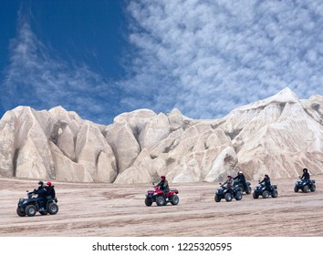 GOREME, TURKEY - JANUARY 8, 2018: Happy chinese tourists enjoying a quad bike ride on the mountains road in countryside over Red Valley in Cappadocia, Central Anatolia.