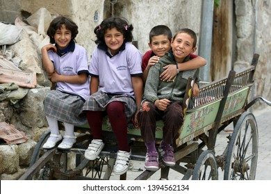 GOREME, TURKEY - MAY 21, 2009 : Smiling children sit in a wooden cart in the village of Goreme located in the Cappadocia region of Turkey.