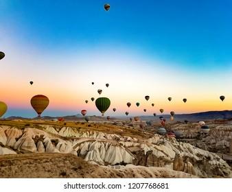 GOREME, TURKEY - SEPTEMBER 24, 2018: Hot air balloons flying at sunrise over Cappadocia, Turkey