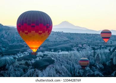 Goreme, Turkey-February 19, 2019 : Hot air balloon flying over rock landscape at Cappadocia Turkey.