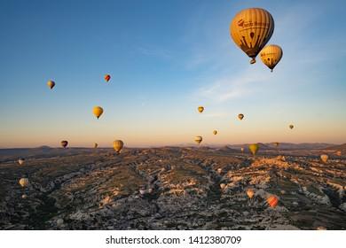 Goreme, Turkey-May 14, 2019 : Hot air balloon flying over rock landscape at Cappadocia Turkey. - Image
