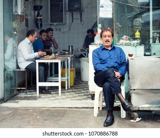Gorgan, Iran - July 27, 2016 : Elegant man sitting in front of a traditional restaurant located in city bazaar