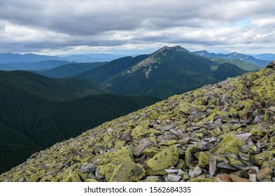 Gorgany mountain range and view to Dovbushanka mountain. Hiking Natural green scenery of cloud stones with moss on mountain slopes that look as valley on background. Carpathian mountains, Ukraine.