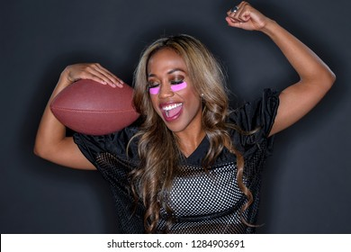 A gorgeous African American model wearing a helmet and holding a football