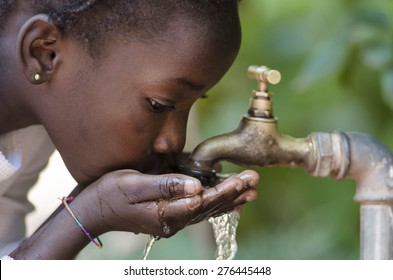Gorgeous African Black Girl Drinking with Hands Cupped (Drought Symbol)  Young African girl drinking clean water from a tap. Water pouring from a tap in the streets of the African city Bamako, Mali.