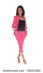 A gorgeous African woman standing in a pink suit with long curly