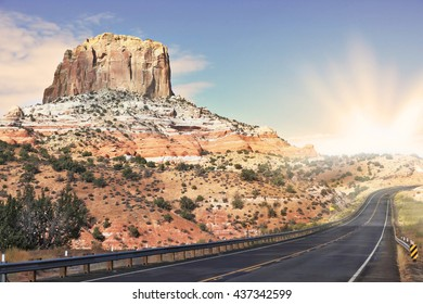 Gorgeous American Highway. Monument Valley in Utah on a cloudy windy day. Shining rays of evening sun sharp light the way