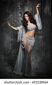 Gorgeous arabian woman bellydancer dancing in white bellydance costume over black studio background. Sexy turkish belly dancer posing in bridal baladi dress with jewelry.