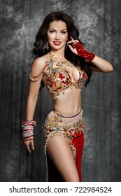 Gorgeous arabian woman bellydancer dancing in traditional bellydance costume over black studio background. Sexy turkish belly dancer posing in bridal baladi dress with jewelry.